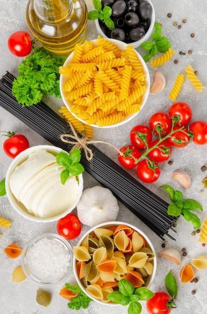 Italienischer lebensmittelhintergrund mit rohen nudeln, frischen tomaten, basilikum, schwarzen spaghetti, oliven, mozzarella, olivenöl, knoblauch und petersilie. Premium Fotos
