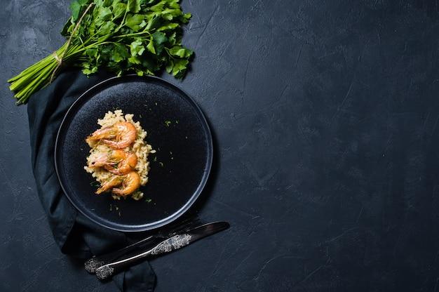 Italienischer risotto mit garnelen auf einem schwarzen teller, ein bündel koriander. Premium Fotos