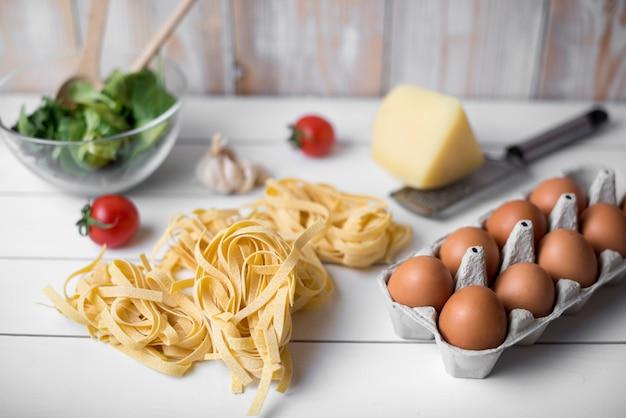 Italienischer roher lebensmittelbestandteil und braunes ei über hölzerner planke Kostenlose Fotos