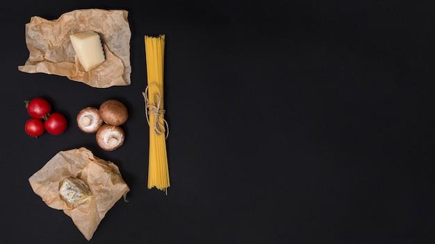 Italienischer spaghettiteigwarenbestandteil mit kopienraum auf schwarzer oberfläche Kostenlose Fotos