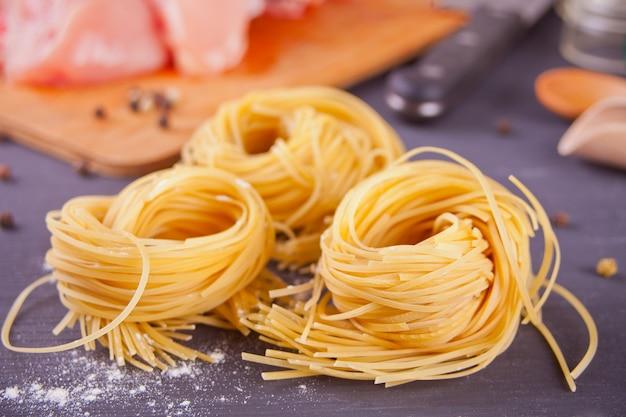 Italienisches ei-teigwarennest auf schwarzem hintergrund Premium Fotos
