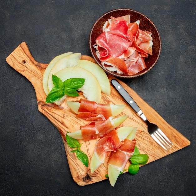 Italienisches essen mit melone und schinken auf holzschneidebrett Premium Fotos
