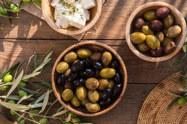 Italienisches essen, mit paprika und grünen oliven, gefüllt mit käse, schwarzen oliven, olivenöl auf holztisch Premium Fotos