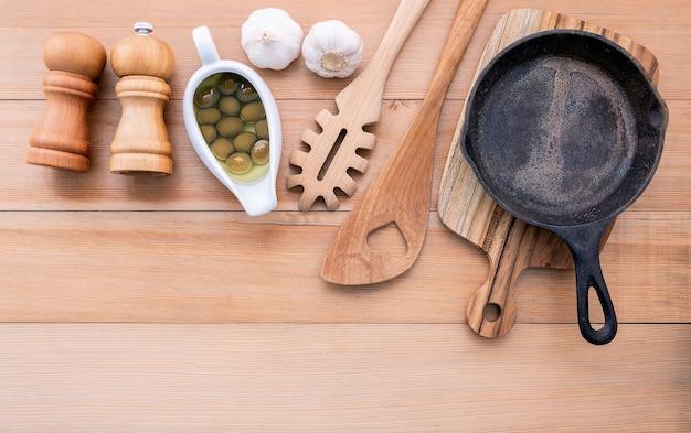 Italienisches nahrungsmittelkonzept und leere roheisenbratpfanne des menüs auf holztisch. Premium Fotos