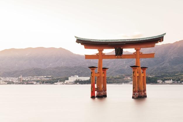 Itsukushima-schrein in einem see, umgeben von grünen hügeln in japan Kostenlose Fotos