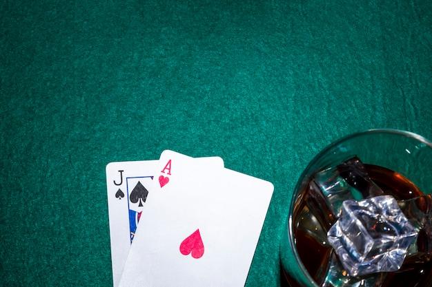 Jack der spaten- und herzass-spielkarte mit whiskyglas auf schürhakentabelle Kostenlose Fotos