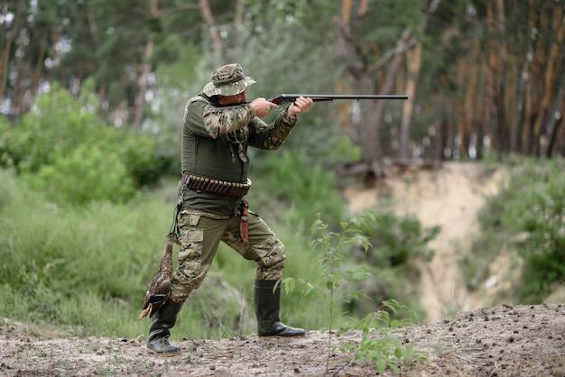 Jäger mit gewehr bei der vogeljagd im sommerwald. Premium Fotos