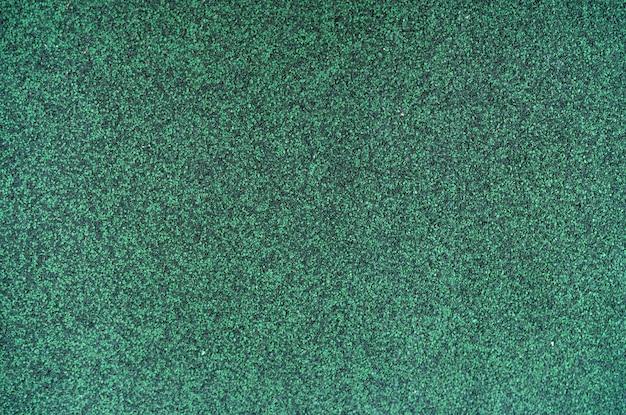 Jägergrüne farbe schindeldach textur hintergrund. dachmaterial. dichte der rauen dunkelgrünen granulatoberfläche des schindeldachtexturhintergrunds. schindeldach aus asphalt, kunststofffaser. Premium Fotos