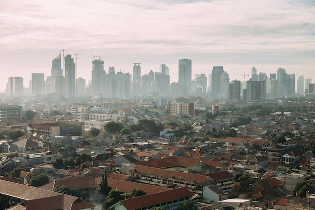 Jakarta-stadtbild mit hochhaus, wolkenkratzern und lokalen dachgebäuden mit rotem ziegeldach und nebel. Premium Fotos