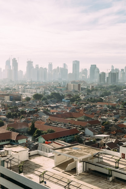 Jakarta-stadtbild mit hochhaus, wolkenkratzern und roten ziegeldächern Premium Fotos