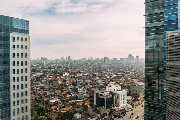 Jakarta-stadtbild mit hochhaus, wolkenkratzern und roten ziegeldächern. Premium Fotos