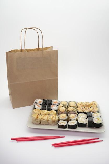 Japanische lebensmittellieferung, sushi-satz und bastelpaket auf einem isolierten hintergrund Premium Fotos
