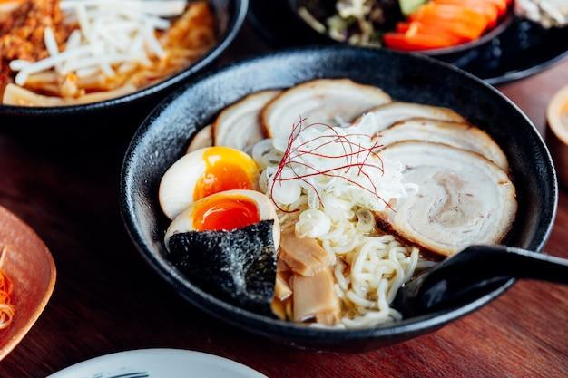 Japanische nudel in miso-suppe mit chashu-schweinefleisch, gekochtes ei, trockene meerespflanze. Premium Fotos