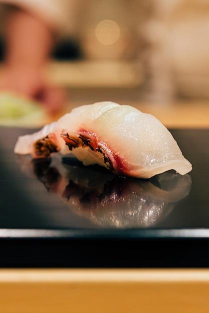 Japanische omakase mahlzeit: close up tai (seebrassen fisch) sushi serviert auf glänzendem schwarzblech. japanische luxusmahlzeit. Premium Fotos