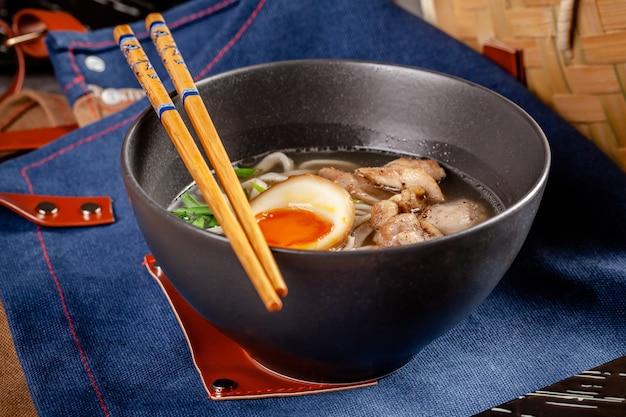 Japanische ramen-suppe mit chinesischen nudeln, ei, huhn und frühlingszwiebeln. Premium Fotos