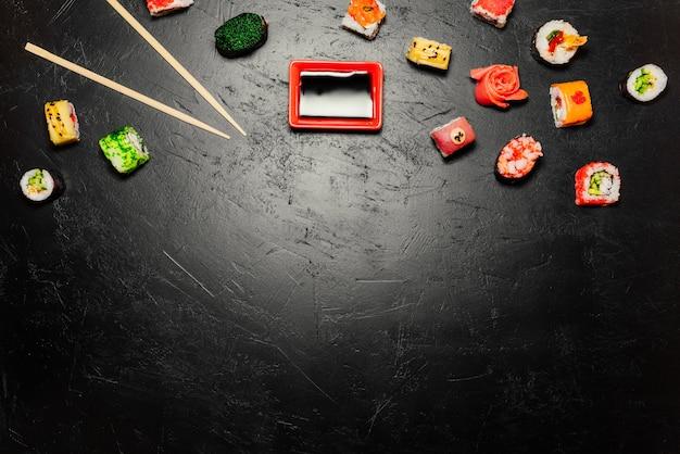 Japanische sushi und essstäbchen auf schwarzem hintergrund. sushi rollen, nigiri, maki Kostenlose Fotos