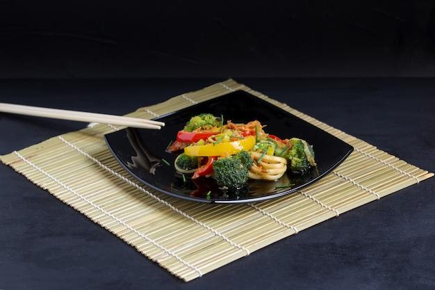 Japanische udonnudeln auf einem schwarzblech mit gemüse und sojasoße auf einer bambusmatte Premium Fotos