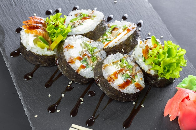 Japanisches restaurant, sushirolle auf schwarzer schieferplatte. Premium Fotos