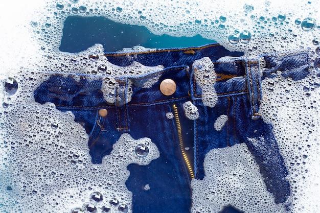 Jeans in pulverförmigem waschmittel einweichen, wasser auflösen. wäscherei-konzept Premium Fotos