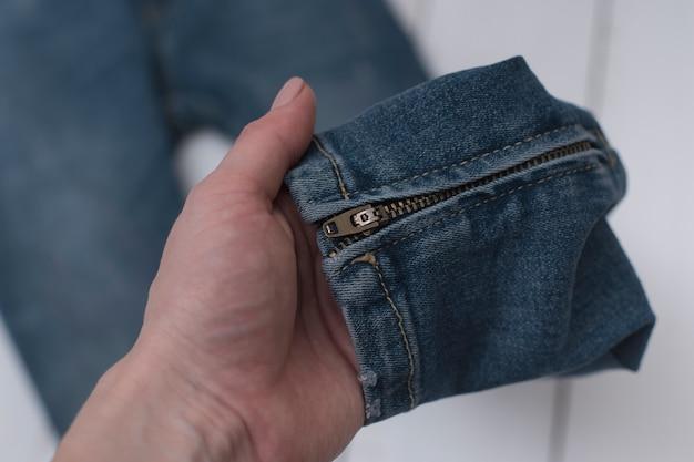 Jeans mit einem reißverschluss in einer weiblichen hand. Premium Fotos