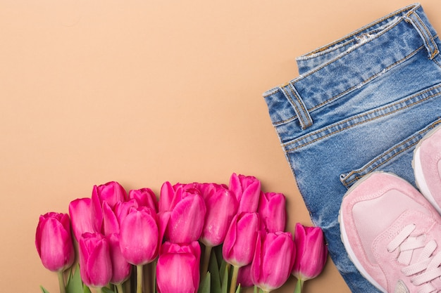 Jeans, turnschuhe und rosa tulpen. flach legen mode frühling konzept Premium Fotos