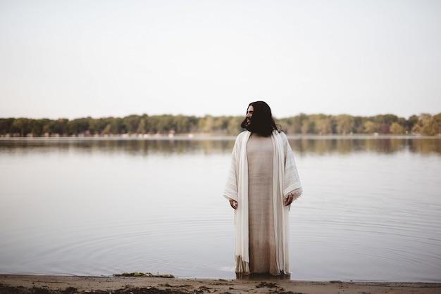 Jesus christus steht im wasser in ufernähe und schaut in die ferne Kostenlose Fotos
