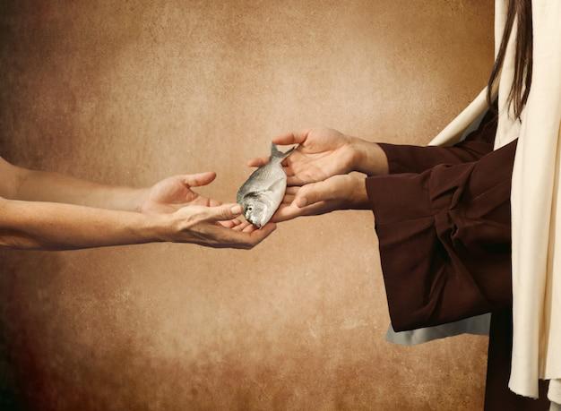 Jesus gibt den fisch einem bettler Premium Fotos