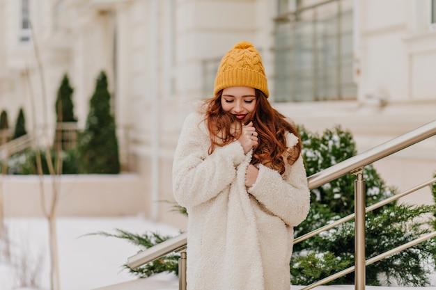 Jocund weißes mädchen, das im winter aufwirft. liebenswerte junge dame, die nahe grüner tanne steht. Kostenlose Fotos