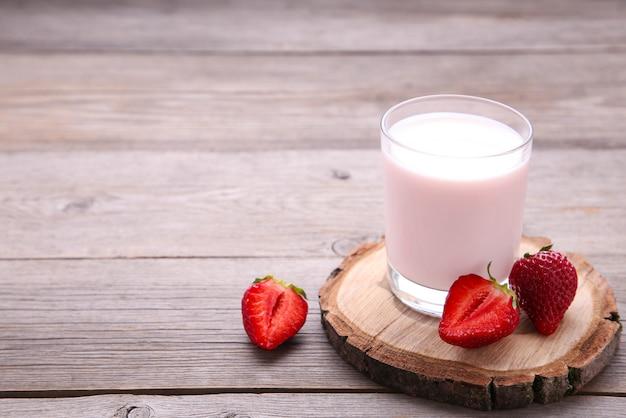 Joghurt mit erdbeere im glas auf grauem holz Premium Fotos