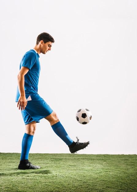 Jonglierender ball des jungen fußballspielers Kostenlose Fotos