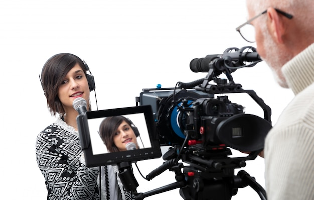 Journalist der recht jungen frau, der bericht im fernsehstudio über weiß vorlegt Premium Fotos