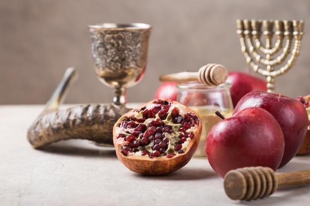 Jüdischer feiertag rosch haschana hintergrund mit honig und apfelscheiben auf holztisch. Premium Fotos