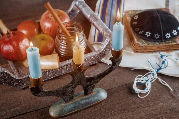 Jüdischer feiertag rosh hashanah jüdisches neues jahr und kerzen auf jüdischem religiösem symbol des gebets-schal tallit Premium Fotos