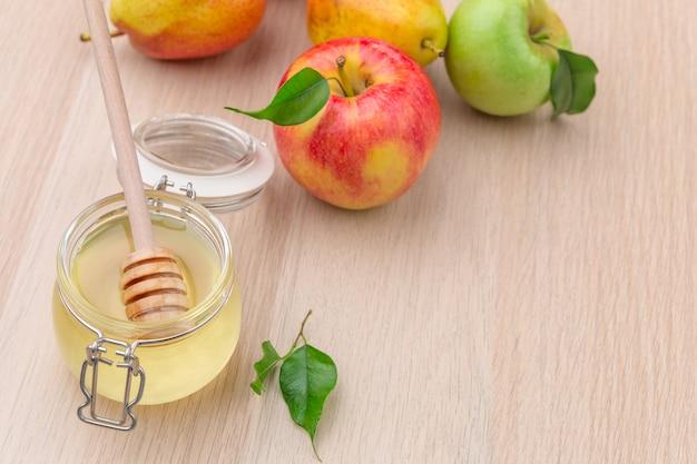 Jüdischer feiertag rosh hashanah mit honig und äpfeln auf holztisch. Premium Fotos