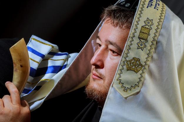 Jüdischer mann bläst das schofarhorn von rosch haschana neujahr Premium Fotos