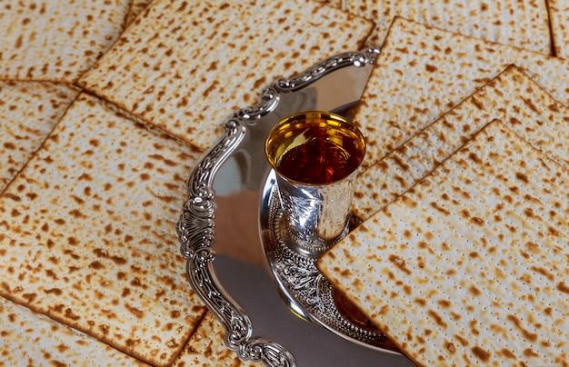 Jüdisches feiertagsbrot des passahfestmatzoh, koscherer wein der gläser über holztisch. Premium Fotos
