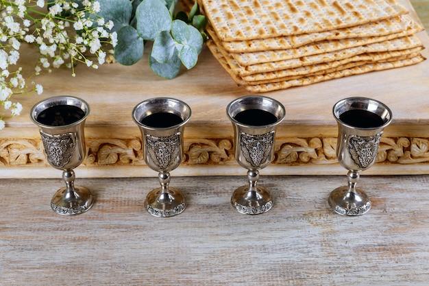 Jüdisches feiertagsbrot des passahfestmatzoh, koscherer wein mit vier gläsern über holztisch. Premium Fotos