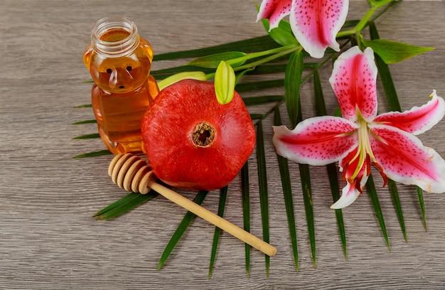Jüdisches feiertagskonzept rosh-haschanah - jüdisches lebensmittel der granatapfelhonigosa-lilien, symbol Premium Fotos