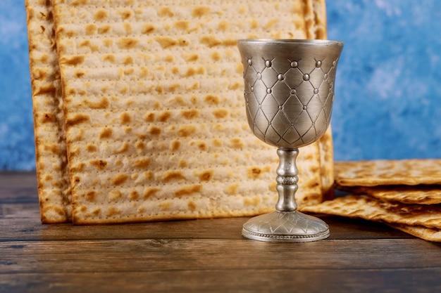 Jüdisches matzebrot mit tasse wein auf pessachfeiertagskonzept der holzoberfläche Premium Fotos