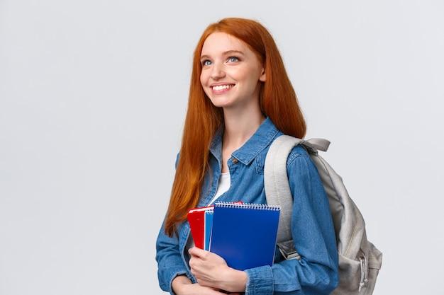 Jugend-, jugend- und bildungskonzept. entschlossen gut aussehende verträumte und optimistisch lächelnde rothaarige studentin mit notizbüchern und rucksack, die sich auf ein neues thema in der klasse freut Premium Fotos