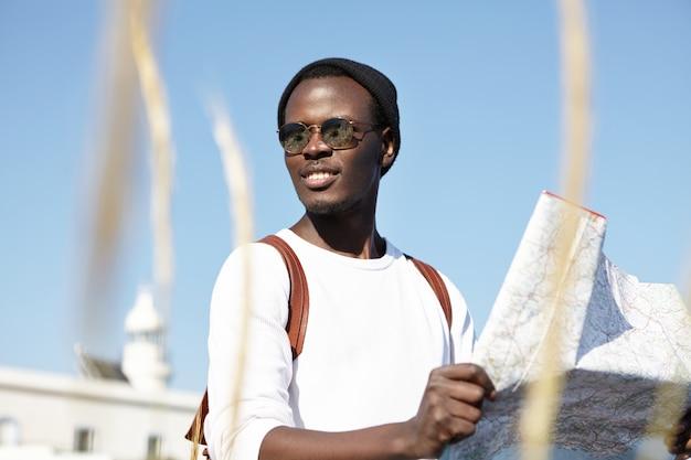 Jugend- und sommerferien. afrikanischer rucksacktourist hält karte, untersucht neue richtungen seiner reise, sieht fröhlich, sorglos und absolut glücklich aus, fühlt sich lebendig auf reisen, trägt spiegelschirme Kostenlose Fotos