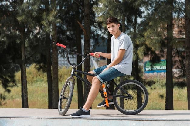 Jugendjunge, der auf fahrrad am park sitzt Kostenlose Fotos