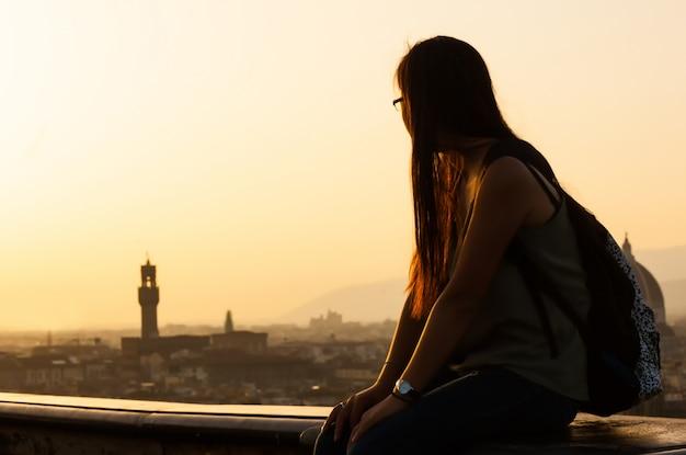 Jugendlich bei sonnenuntergang die ansicht von florenz aufpassend. Premium Fotos