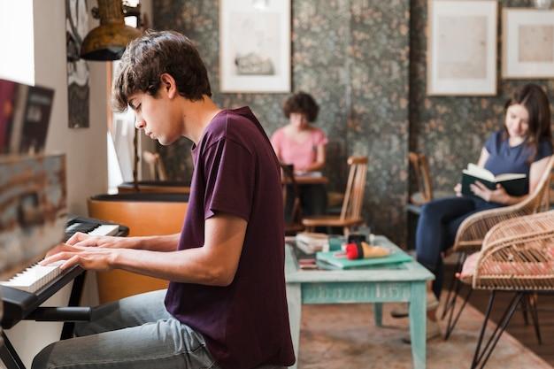 Jugendlich junge, der klavier im kaffee spielt Kostenlose Fotos
