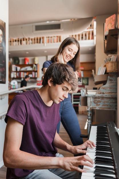 Jugendlich mädchen, das auf den freund spielt klavier hört Kostenlose Fotos