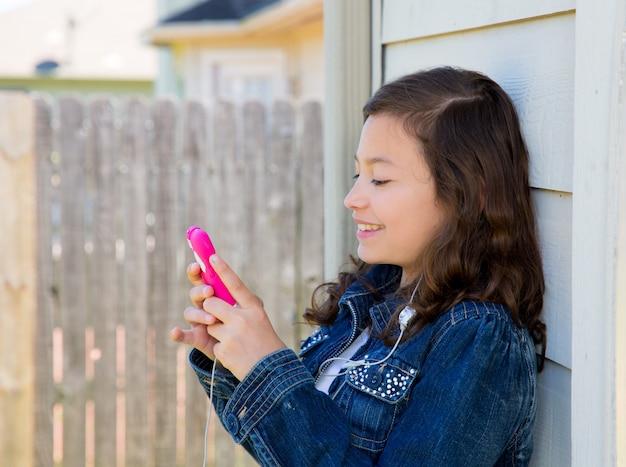 Jugendlich mädchen, das musik mit smartphone earings spielt Premium Fotos