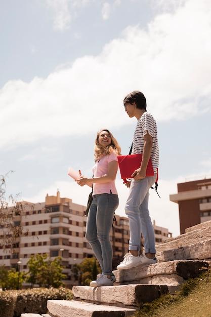 Jugendlich paare auf treppen gegen stadtbild Kostenlose Fotos