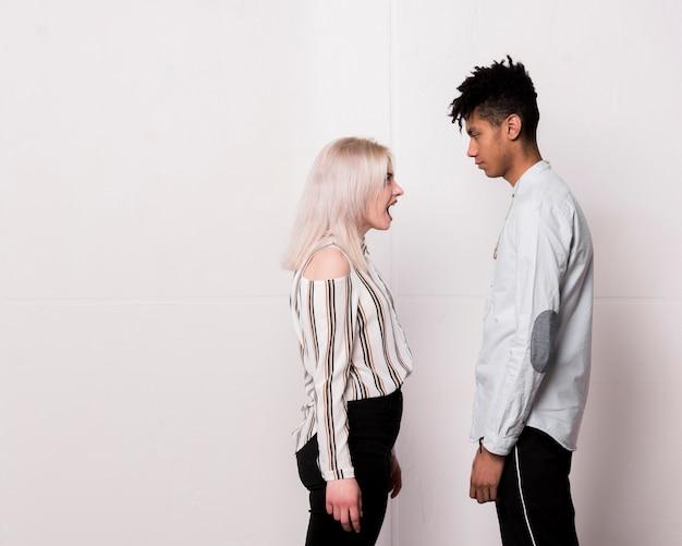 Jugendliche, die auf ihrem freund ernsthaft betrachtet ihn gegen weißen boden schreit Kostenlose Fotos