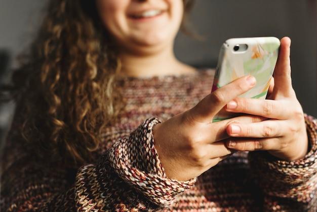 Jugendliche, die einen smartphone auf einem sozial- und neigungskonzept des betts verwendet Kostenlose Fotos