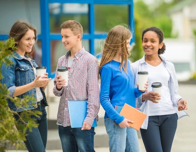 Jugendliche, die kaffee am park nach lektionen trinken. Premium Fotos